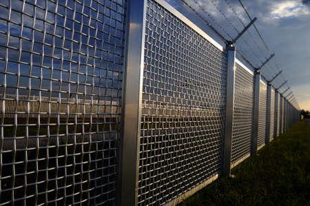 carcel: Parte de metal cerca de una valla de rejilla metálica con alambre de púas en la parte superior