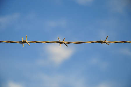 delimit: Barbed wire  Part of a fence with barbed wire under a blue sky