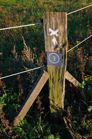 Sign post and pasture fence Old weathered pole of a pasture fence with indications for ramblers photo