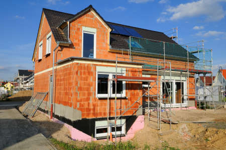 bricklayer: Construction site Construction site with a dwelling house under a blue sky