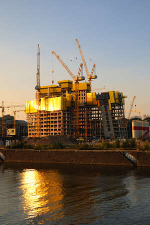 formwork: Big construction site A big construction site with cranes and silos at a river bank