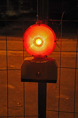 Warning light  Photo of a burning warning light in front of metal grid fence Stock Photo - 12320484