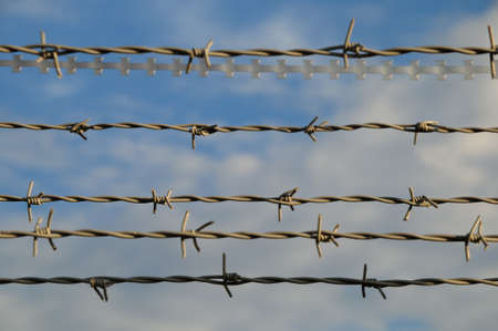 Barbed wire  Part of a fence with barbed wire under a cloudy sky Stock Photo - 16598084