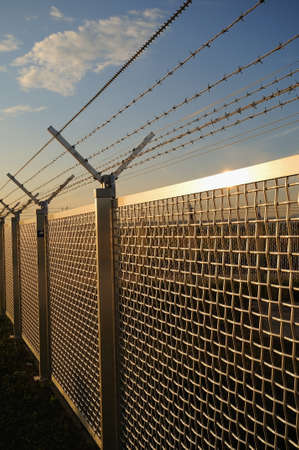 Metal fence Part of a metal grid fence with barbed wire at the top Stock Photo - 15455142
