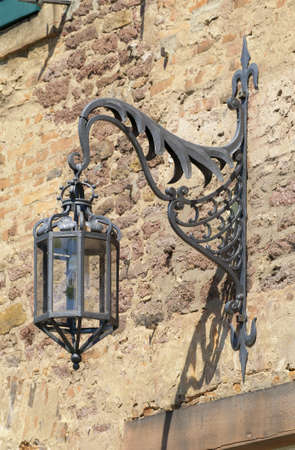 russet: Old arc lamp Old arc lamp fastened at a russet sandstone wall  Stock Photo