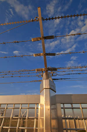 delimit: Part of a fence of barbed wire under a blue sky