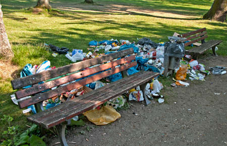 carelessness: park bench with lot of garbage around