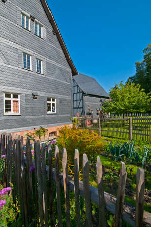 constancy: House with slate wall and garden in a landscape Museum Stock Photo