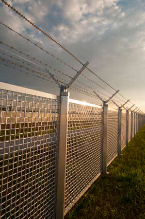 barbed wire fence: Security fence with barbed wire