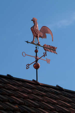 Weathercock made of copper on a roof in front of blue sky photo