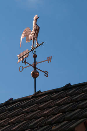 gust: Weathercock made of copper on a roof in front of blue sky