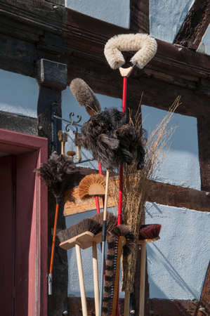 constancy: Brushes Sweepers Brooms Dusters in front of halftimbered House Stock Photo