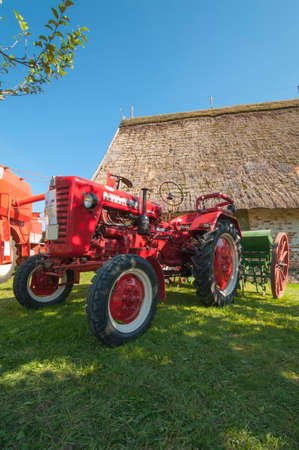 half timbered house: Ancient tractor in front of a half timbered house Stock Photo