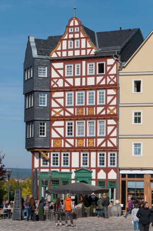 continuation: White halftimbered house with slate roof and beams redpainted wallcover cafe on the ground floor in a city Village Stock Photo