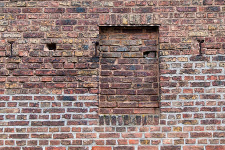 porous brick: Part of an old brick wall in brown with walled window