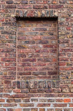 industrialization: Part of an old brick wall in brown with walled window