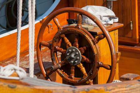 route master: Single wooden steering wheel at an ancient sailing boat