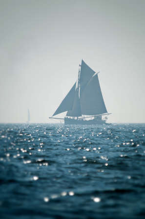 Sailing boat far away silhouette with deep blue sea in front photo
