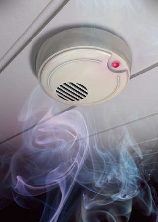 A smoke detector installed at a ceiling with smoke