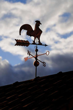 Weathercock made of copper on a roof in front of cloudy sky photo