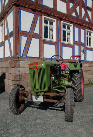 oldtimer: tractor old in front of a half timbered house