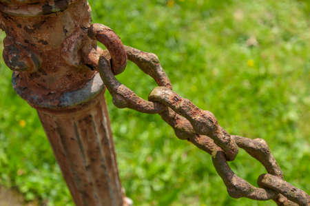 forged rusty chain and pole