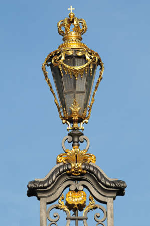 Ancient lantern with golden crown at fence