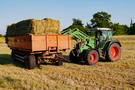 Green tractor loading hay bales on a trailer