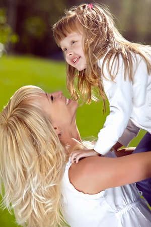 playful behaviour: Mother playing with her daughter in the park