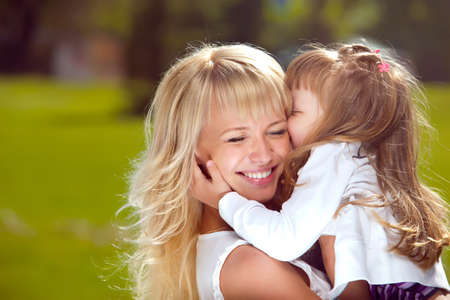 playful behaviour: Beautiful happy mother with her daughter outdoors