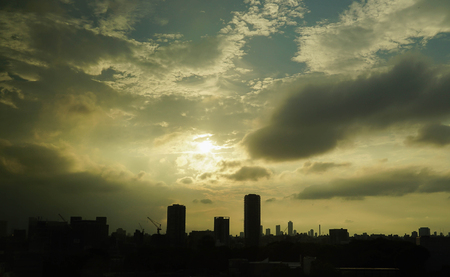 peaking: silhouette photo of Moden City with Sunset Sky Stock Photo