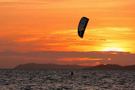 kiting: Kite-surfing on orange sunset s background at pattaya,Thailand
