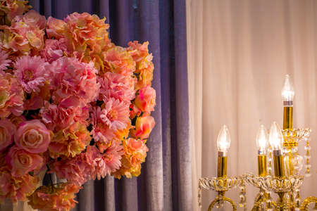 The pink flowers in the room with the electronic candle light with gray curtain , romantic retro style, lowkey. Stock Photo