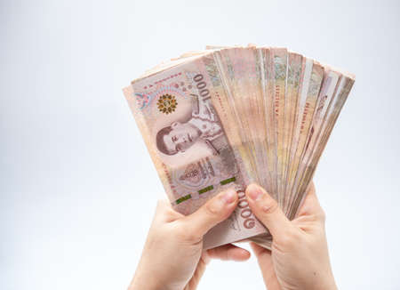 Hand holding thai money over white background, Soft focus, copy space. Stock Photo
