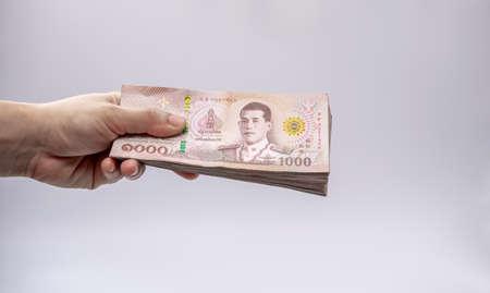 Hand holding Thai money isolated white background Reklamní fotografie