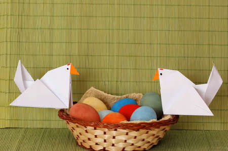 Genuine eggs and origami hens on a small basket photo