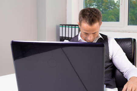 creativ: young business man working at a laptop and fall to sleep