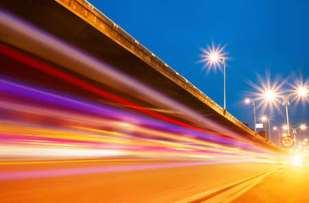 busy life: High speed traffic and blurred light trails under the overpass at night scene