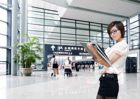 airport arrival: Young business woman on the background of a modern airport Editorial