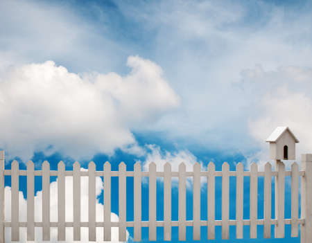 white fence with bird house and blue sky photo