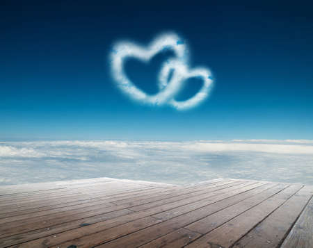 Two heart shaped clouds in the blue sky photo