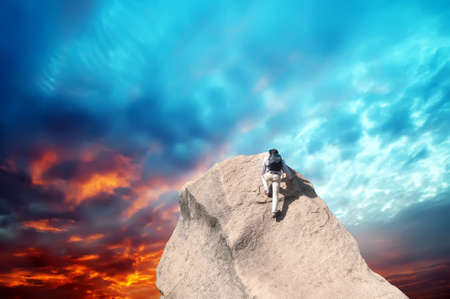 Young man climbing on a limestone wall with blue sky on the background Foto de archivo