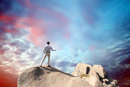Young man standing on cliff Stock Photo