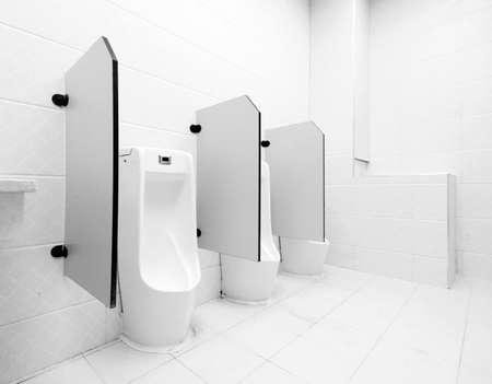 latrine: white porcelain urinals in public toilets