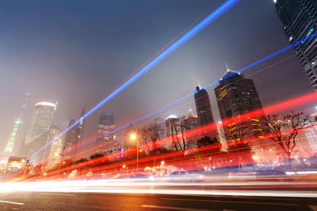 the light trails on the modern building background in shanghai china.  Archivio Fotografico