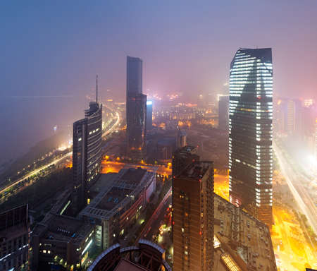 Bird view at Nanchang China  Skyscraper under construction in foreground  Fog, overcast sky and pollution  Bund  Nanchang  area photo