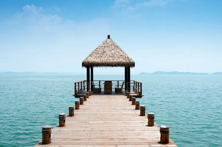 Wooden jetty over the beautiful Maldivian sea with blue sky photo