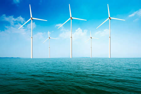 white wind turbine generating electricity on sea photo
