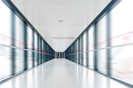 A long pedestrian tunnel, modern building interior. Stock Photo