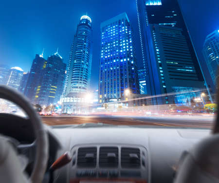 Drivers hands on a steering wheel of a car and night scene photo